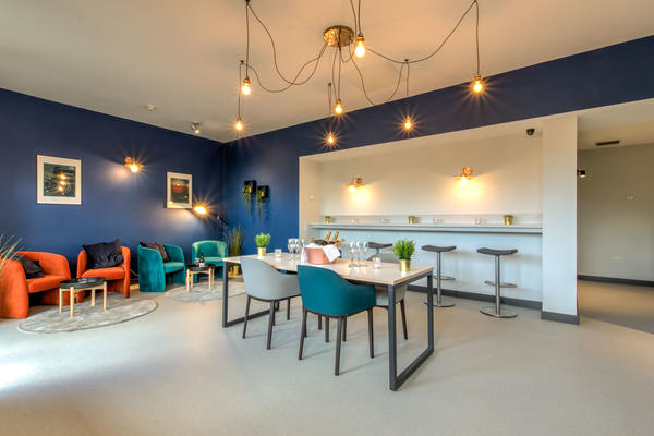 Photo of a bar seating area with dark blue walls, a striking modern light fitting, and various chairs and tables around the room