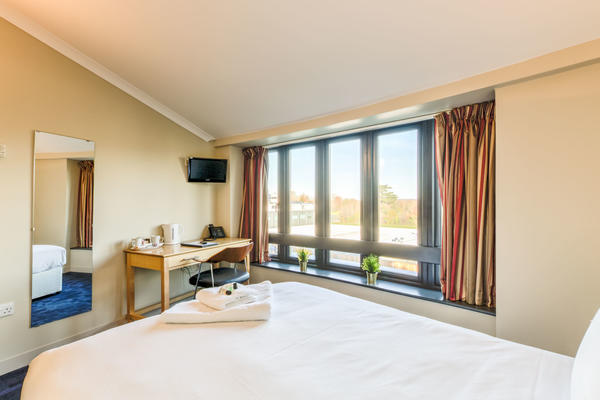 Photo of a hotel room with double bed, mirror, desk, TV and large windows